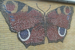 """Dagpåfugleøje, vægudsmykning i mosaik, udført af Marie Elisabeth A. Franck Mortensen, """"De Kreative Mellemrum"""""""